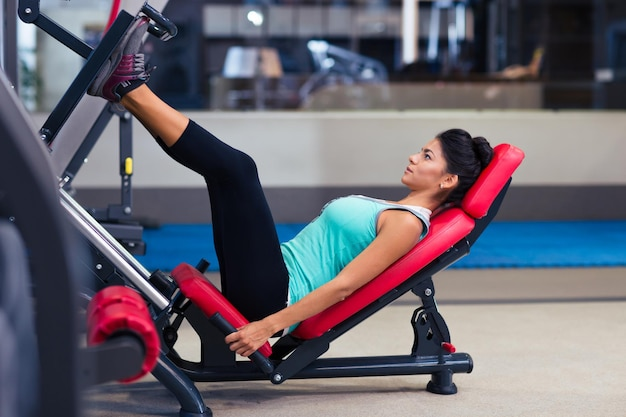 Portrait d'une séance d'entraînement de femme de remise en forme sur la machine d'exercices dans la salle de sport