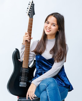 Portrait d'un séduisant jeune adolescent thaï-turc souriant assis et tenant la guitare électrique sur l'amplificateur. guitariste junior fille regardant la caméra isolée en fond blanc
