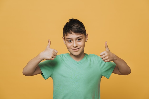 Portrait de séduisant jeune écolier vêtu d'un t-shirt vert, mignon souriant montrant les pouces vers le haut
