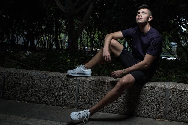Portrait de séduisant jeune homme assis sur une marche