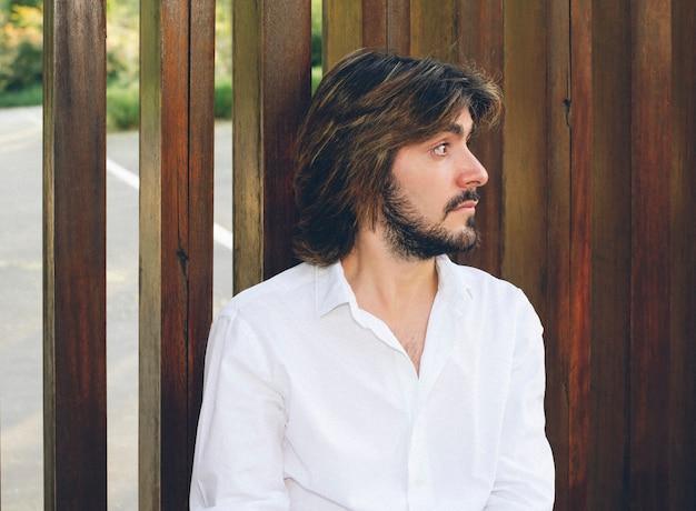 Portrait de séduisant jeune homme aux cheveux longs et à la barbe, vêtu d'une chemise blanche.