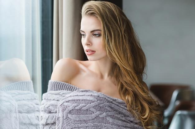 Portrait de séduisante jeune femme blonde aux cheveux longs enveloppée dans une couverture tricotée grise