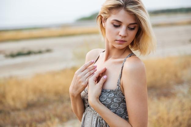 Portrait de séduisante jeune femme sensuelle debout à l'extérieur