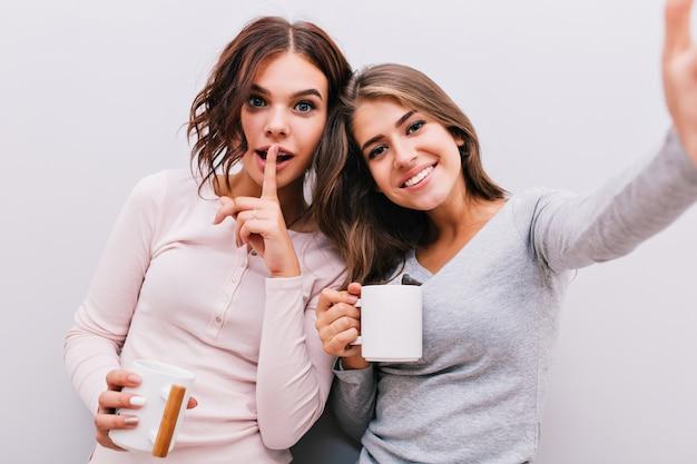 Portrait de selfie de deux jeunes filles en pyjama avec des tasses sur un mur gris. fille aux cheveux bouclés a mis le doigt sur les lèvres, ils sourient.