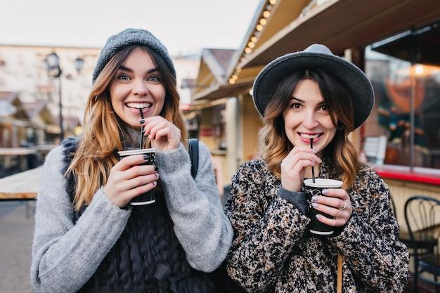 Portrait de selfie de femmes à la mode joyeuses s'amusant sur une rue ensoleillée de la ville. look élégant, s'amuser, voyager avec des amis, sourire, exprimer de vraies émotions positives.