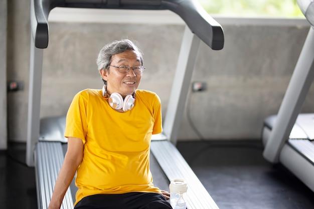 Portrait de senior avec des lunettes faisant de l'exercice dans une salle de fitness.