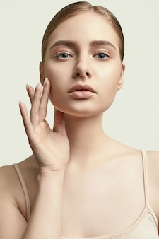Portrait sensuel du modèle de femme glamour avec une peau propre posant sur blanc