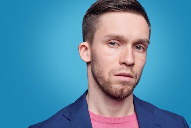 Portrait de sérieux beau jeune homme barbu aux yeux bleus