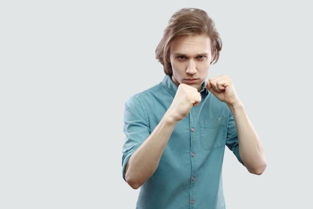 Portrait de sérieux beau jeune homme blond aux cheveux longs en chemise décontractée bleue debout dans la pose de poings de boxe et regardant la caméra. tourné en studio intérieur, isolé sur fond gris clair.