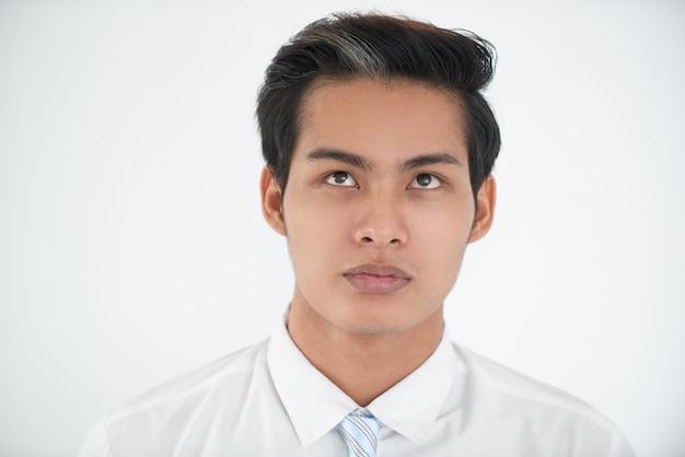 Portrait sérieux d'un jeune homme d'affaires en train de chercher