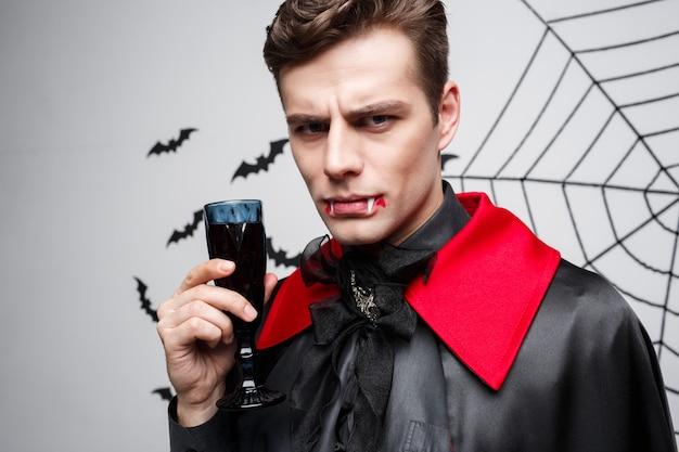 Portrait de sérieux vampire caucasien beau boire du vin rouge sanglant.