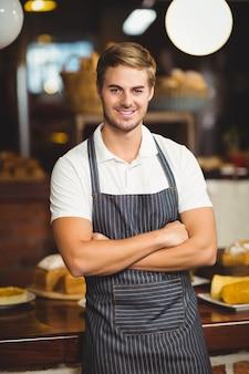 Portrait d'un serveur avec les bras croisés au café