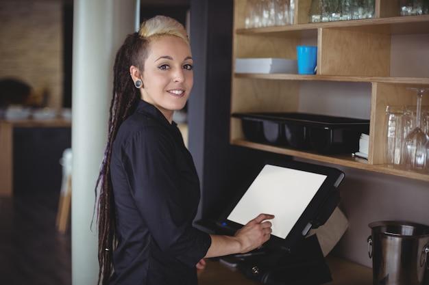 Portrait de serveuse à l'aide d'une caisse enregistreuse au comptoir