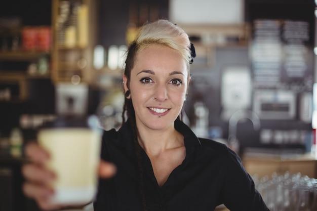 Portrait de serveuse debout avec une tasse de café jetable
