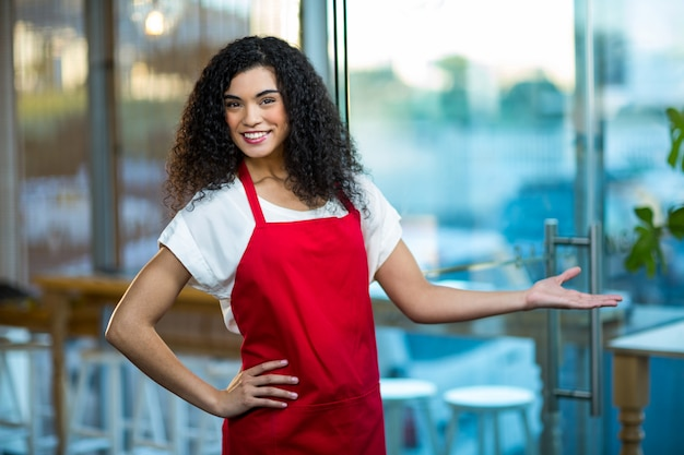 Portrait de serveuse souriante debout avec la main sur la hanche