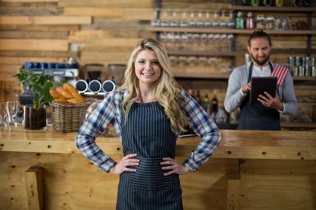Portrait de serveuse souriante debout avec les mains sur la hanche au comptoir