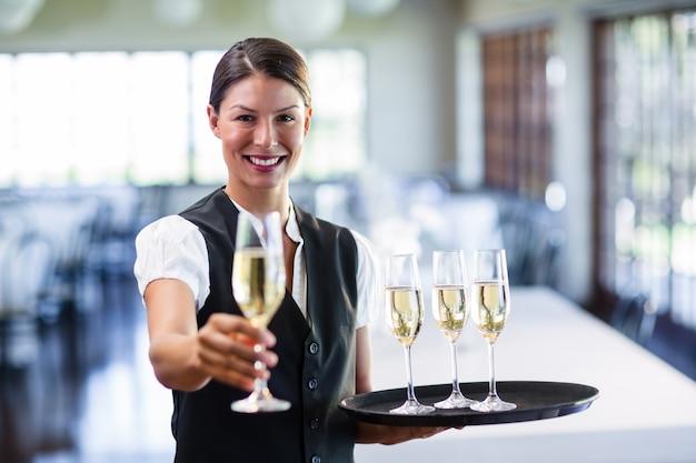 Portrait de serveuse souriante offrant un verre de champagne