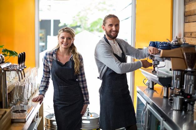 Portrait de serveuse souriante et serveur travaillant au comptoir