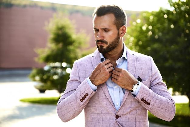 Portrait de sexy beau mannequin homme d'affaires habillé en costume élégant posant sur fond de rue. métrosexuel