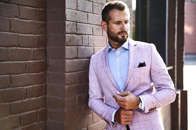 Portrait de sexy beau mannequin homme d'affaires habillé en costume élégant posant près du mur de briques sur le fond de la rue. métrosexuel