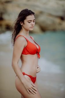 Portrait de sexy belle femme bronzée posant en bikini maillot de bain coloré sur la côte de la mer.