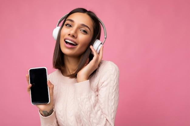 Portrait de sexy belle jeune femme brune mignonne portant un pull rose isolé sur rose