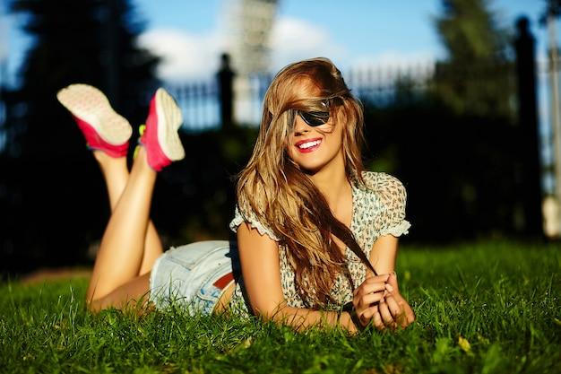 Portrait, de, sexy, mignon, drôle, jeune, élégant, sourire, femme, girl, modèle, dans, vif, moderne, tissu, à, parfait, bain de soleil, corps, dehors, mensonge, dans parc, sur, herbe verte, dans, jean, short, dans, lunettes
