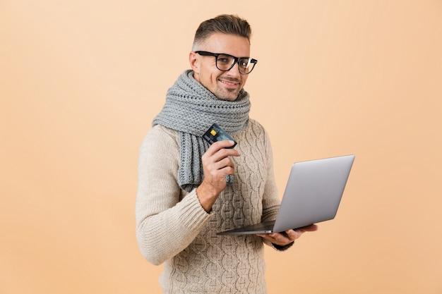 Portrait si un homme heureux habillé en pull et écharpe debout isolé sur un mur beige, tenant un ordinateur portable, montrant une carte de crédit en plastique