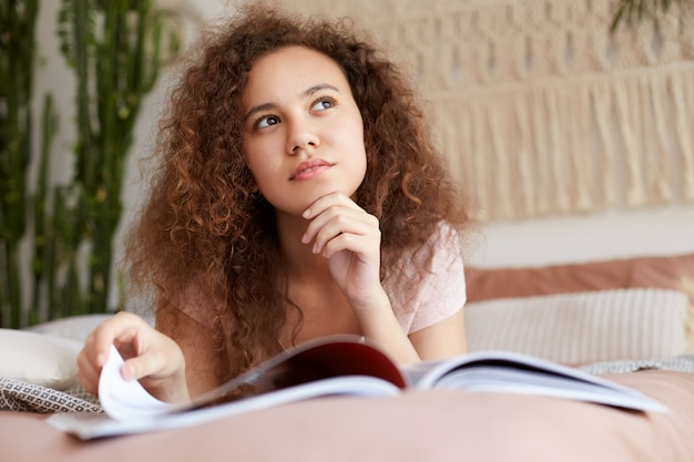 Portrait si rêvant jeune fille afro-américaine reposée aux cheveux bouclés, se trouve sur le lit et lit un nouveau numéro de magazine, détourne les yeux et touche le menton.