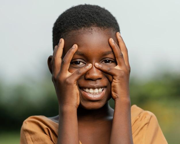 Portrait smiley enfant africain tenant les mains sur le visage