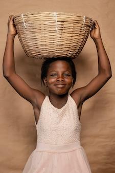 Portrait smiley girl avec panier de paille sur la tête