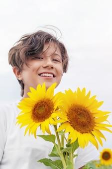Portrait smiling teen girl avec des fleurs de tournesol à l'extérieur, l'heure d'été