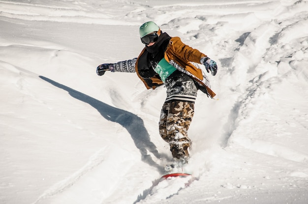 Portrait de snowboarder en tenue de sport dévalant la pente enneigée