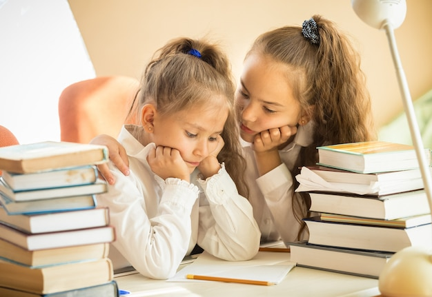 Portrait de sœur aînée apaisante plus jeune tout en faisant ses devoirs