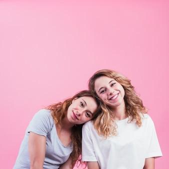 Portrait de soeur souriante se penchant tête sur fond rose