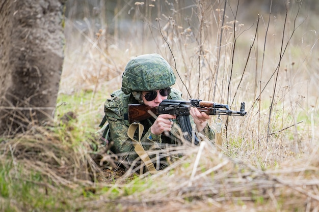 Un portrait d'un soldat entièrement équipé visant avec un fusil sur un champ de bataille au milieu de l'herbe sèche.