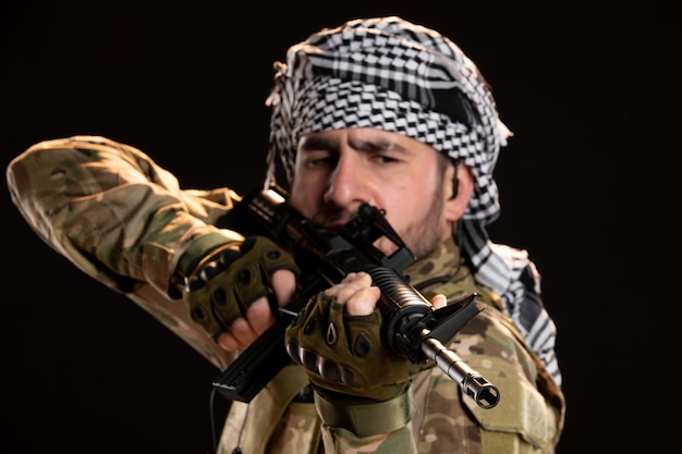 Portrait d'un soldat masculin en camouflage combattant avec une mitrailleuse sur un mur noir