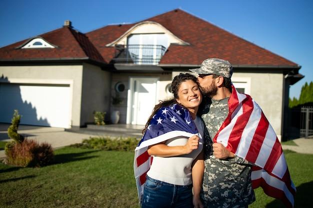 Portrait de soldat en uniforme embrassant sa femme et tenant le drapeau américain devant leur maison