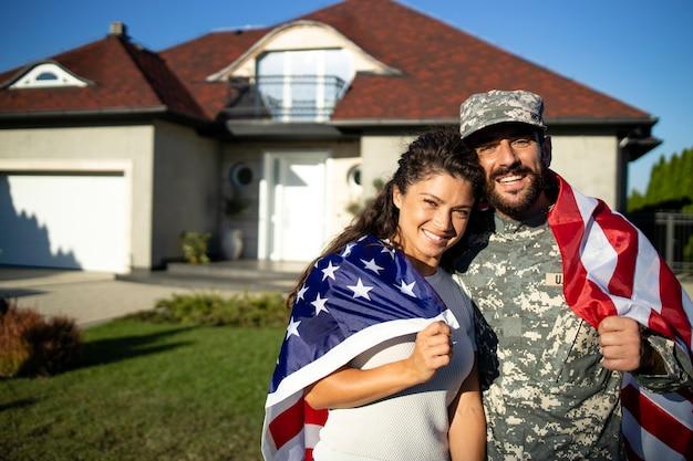 Portrait de soldat en uniforme étreignant sa femme et tenant le drapeau américain devant leur maison