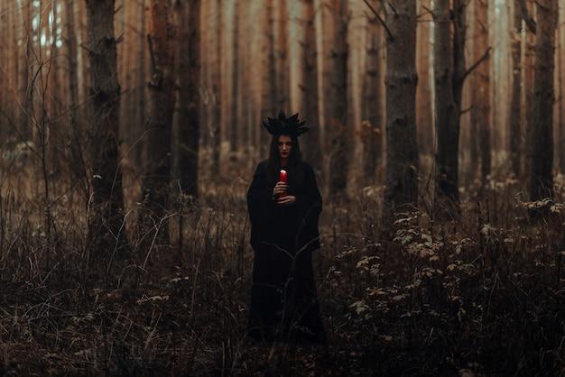 Portrait sombre d'une sorcière en costume noir dans les bois