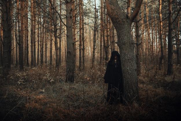 Portrait sombre d'une terrible sorcière en costume noir dans la forêt près d'un arbre
