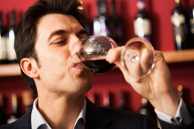 Portrait d'un sommelier dégustant un verre de vin