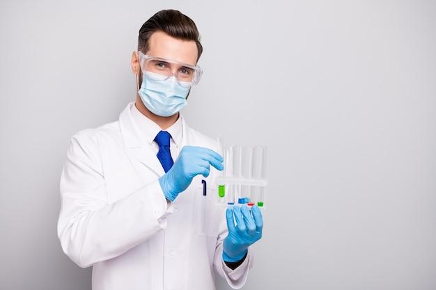 Portrait de son beau chirurgien doc intelligent intelligent attrayant tenant dans les mains des ampoules faisant le laboratoire d'analyse de réaction virale créant un nouveau remède médicamenteux isolé sur couleur pastel gris blanc clair