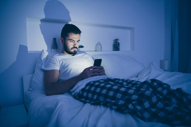 Portrait de son beau gars concentré attrayant allongé sur le lit à l'aide de la cellule d'envoi de sms navigation sur le site web la nuit en fin de soirée maison sombre chambre lumineuse à l'intérieur