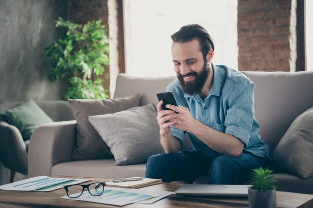 Portrait de son beau mec brunet joyeux joyeux attrayant assis sur un divan en tapant sms bavarder avec sa petite amie au loft industriel chambre intérieure de style moderne à l'intérieur