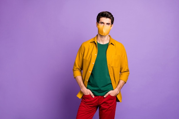 Portrait de son contenu attrayant homme sérieux portant un masque de tendance jaune orange de sécurité chine wuhan mers cov grippe fièvre élevée virus décontamination isolé violet lilas couleur pastel fond