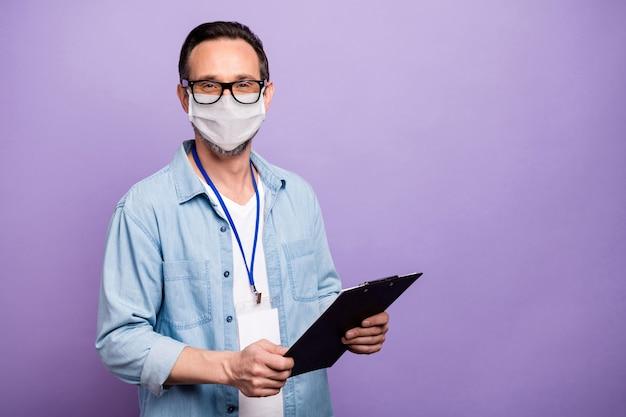 Portrait de son homme caucasien mature tenir un clip board avoir une presse de réunion d'entreprise portant un masque de gaze maladie cov mers mesures préventives médecine isolée sur fond de couleur violet