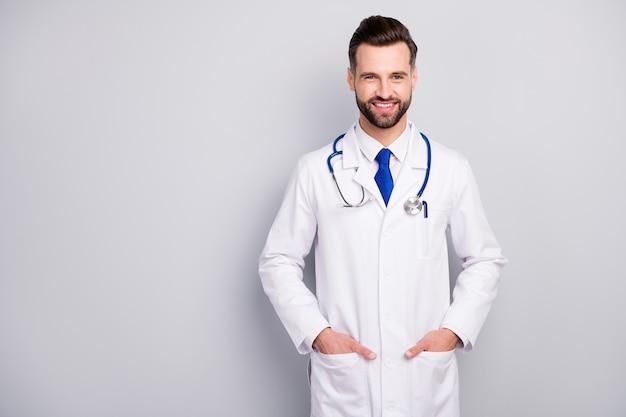Portrait de son il belle attrayante intelligente intelligente qualifiée joyeuse joyeuse joyeux heureux barbu doc propriétaire du centre de diagnostic tenant la main dans les poches isolées sur couleur pastel gris blanc clair