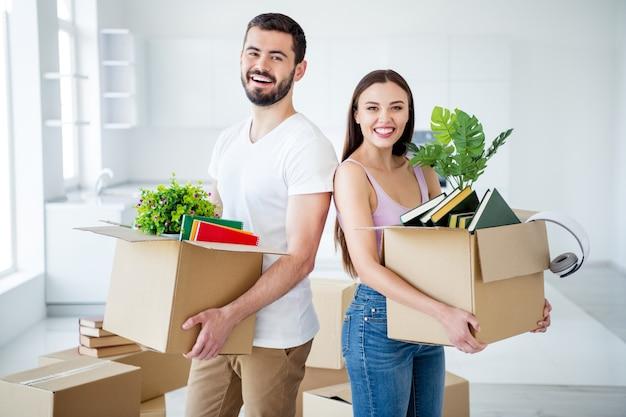Portrait de son il elle elle belle attrayante belle joyeuse joyeuse couple heureux portant un paquet de trucs tenant dans les mains des boîtes au nouvel endroit espace plat lumière blanche maison intérieure ménage à l'intérieur