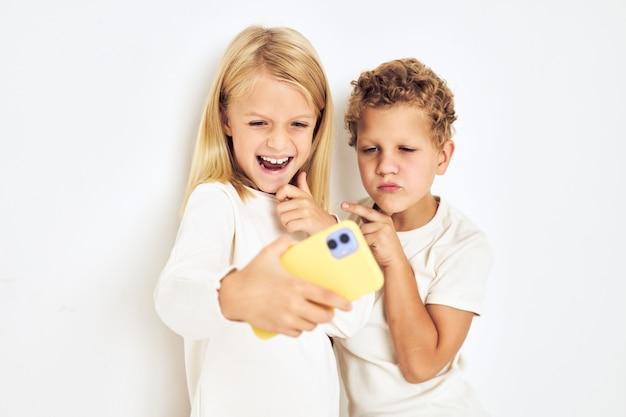 Portrait de son il lui avec l'enfance de style de vie de divertissement de téléphone jaune. photo de haute qualité